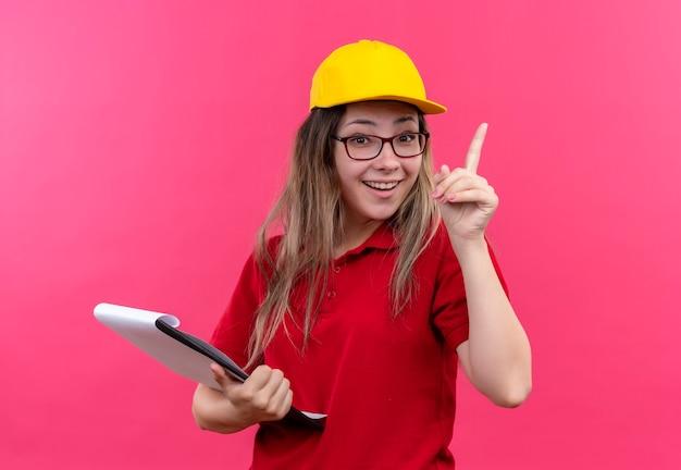 Giovane ragazza di consegna in camicia di polo rossa e cappuccio giallo che tiene appunti che mostra il dito indice che sorride avendo nuova idea