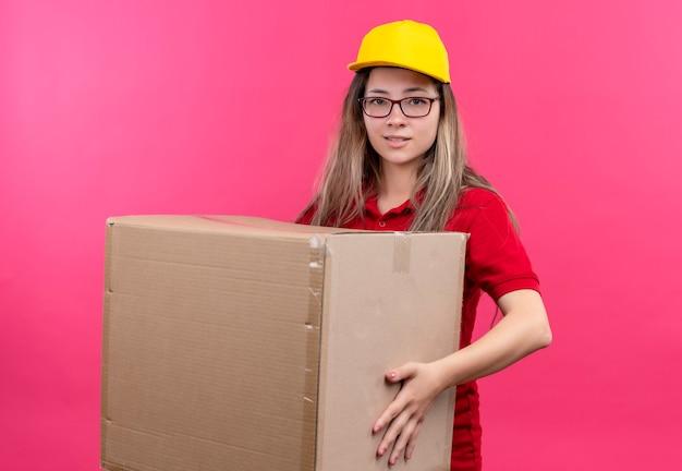 Giovane ragazza di consegna in camicia di polo rossa e cappuccio giallo che tiene grande scatola di cartone che guarda sorridere della macchina fotografica