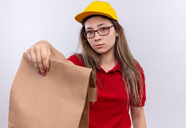 Giovane ragazza di consegna in camicia di polo rossa e cappuccio giallo che tiene il pacchetto di carta che guarda l'obbiettivo con l'espressione sicura seria