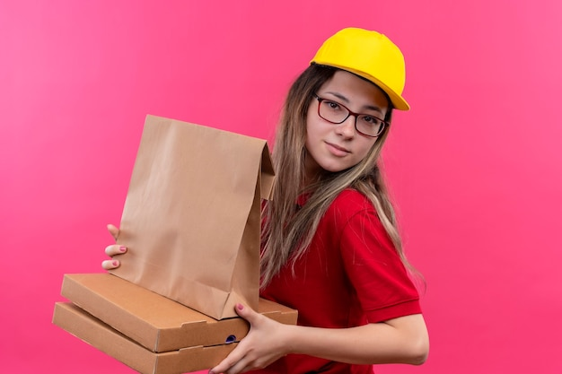 Giovane ragazza di consegna in polo rossa e cappuccio giallo che tiene scatole per pizza e pacchetto di carta che sembra fiducioso