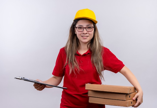 Young delivery girl in red polo shirt and yellow cap holding stack of pizza boxes and clipboard looking at camera with confident smile