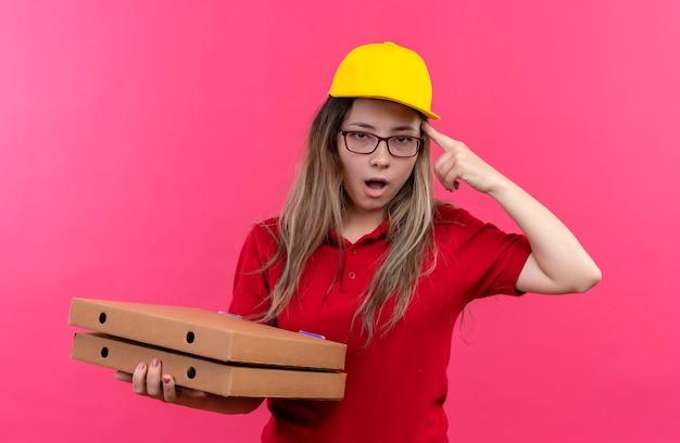 Giovane ragazza delle consegne in maglietta polo rossa e cappuccio giallo che tiene la pila di scatole per pizza che punta la sua tempia, dimenticato, ricorda l'errore, concetto di cattiva memoria