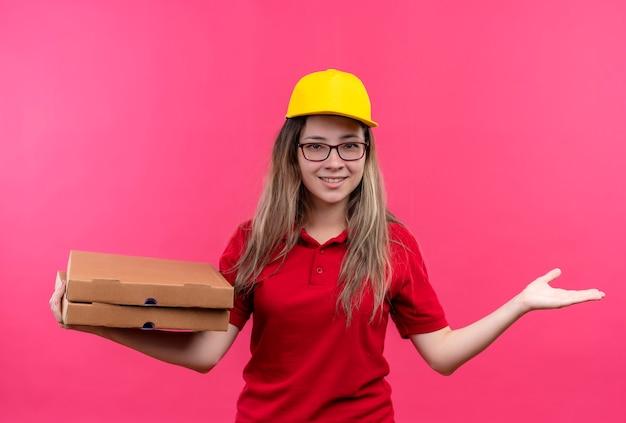 Giovane ragazza di consegna in camicia di polo rossa e cappuccio giallo che tiene pila di scatole per pizza che presenta con il braccio della sua mano che sorride