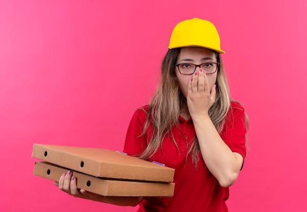 Giovane ragazza delle consegne in polo rossa e cappuccio giallo che tiene la pila di scatole per pizza scioccata che copre la bocca con la mano