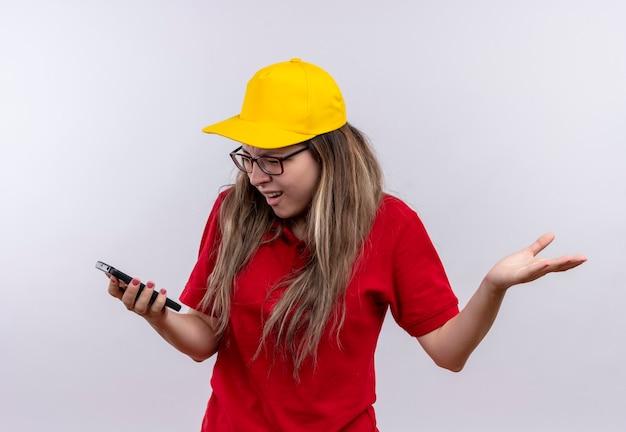 Giovane ragazza di consegna in maglietta polo rossa e berretto giallo guardando lo schermo del suo smartphone frustrato