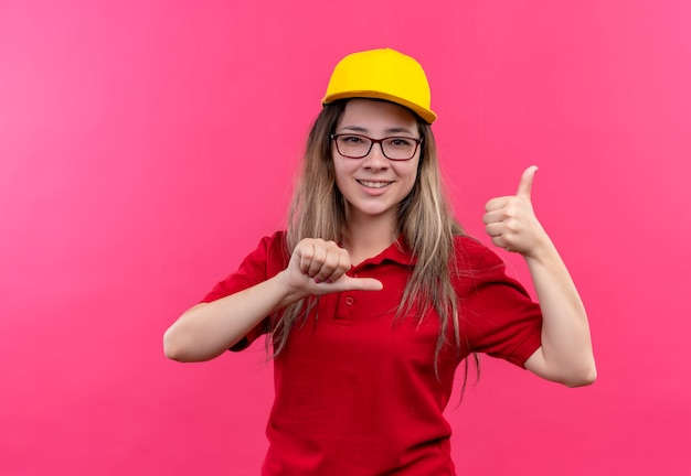 Young delivery girl in red polo shirt and yellow cap pointing to herself self-satisfied and proud showing thumbs up smiling