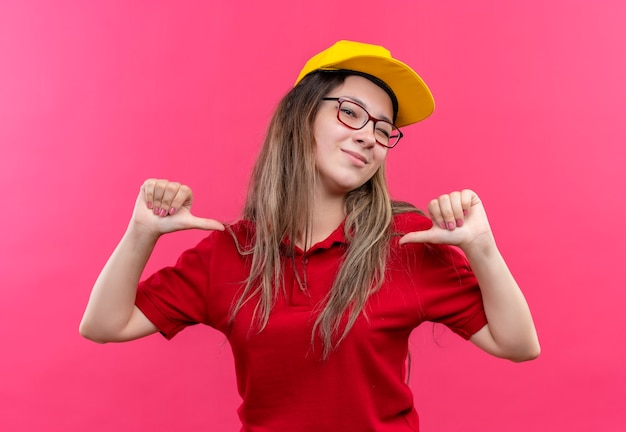 Young delivery girl in red polo shirt and yellow cap pointing to herself self-satisfied and proud