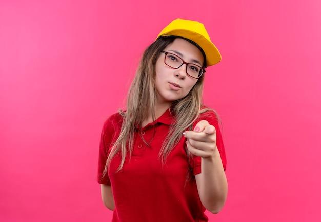 Giovane ragazza delle consegne in polo rossa e cappuccio giallo che punta con il dito indice alla fotocamera