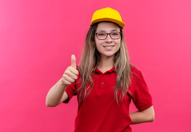 Young delivery girl in red polo shirt and yellow cap smiling showing thumbs up
