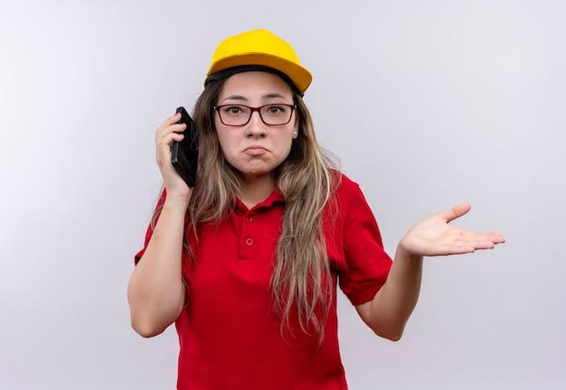 Giovane ragazza di consegna in camicia di polo rossa e cappuccio giallo che parla sul telefono cellulare che sembra scrollata di spalle confuso