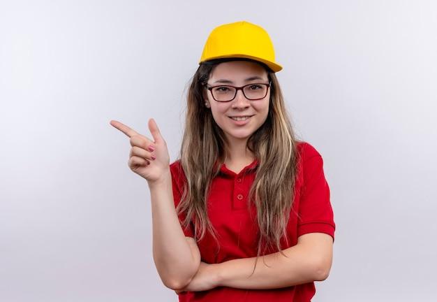 Giovane ragazza di consegna in maglietta polo rossa e giallo sorridente che punta amichevole con il dito a lato