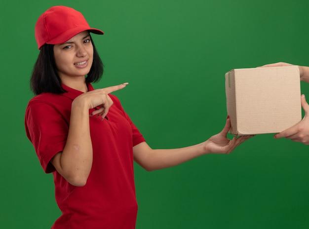 Giovane ragazza delle consegne in uniforme rossa e cappuccio che dà la scatola di cartone a un cliente che è confuso e dispiaciuto che indica con il dito indice a qualcosa che sta sopra la parete verde