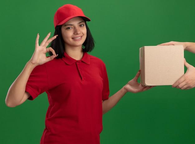 Giovane ragazza di consegna in uniforme rossa e cappuccio che dà la scatola di cartone ad un cliente che sorride amichevole che mostra segno giusto che sta sopra la parete verde