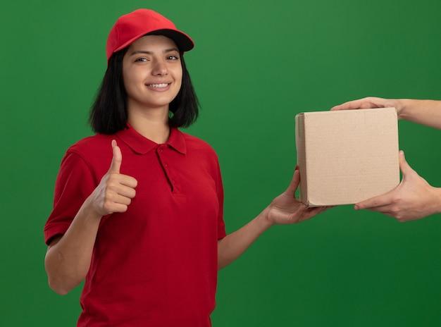 Giovane ragazza di consegna in uniforme rossa e cappuccio che dà la scatola di cartone a un cliente sorridente amichevole che mostra i pollici in su in piedi sopra la parete verde