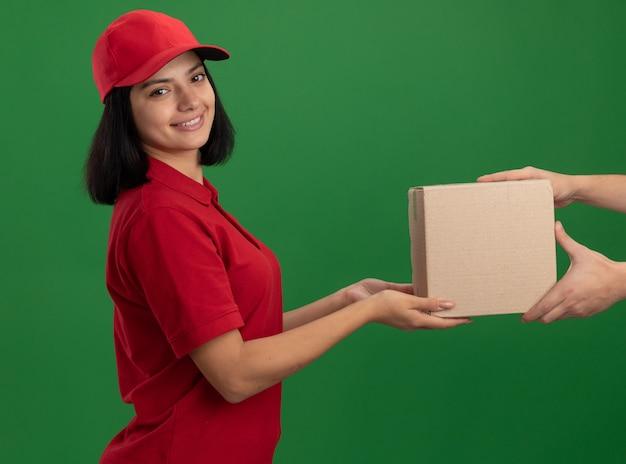 Giovane ragazza delle consegne in uniforme rossa e cappuccio che dà la scatola di cartone a un cliente sorridente in piedi amichevole sopra la parete verde