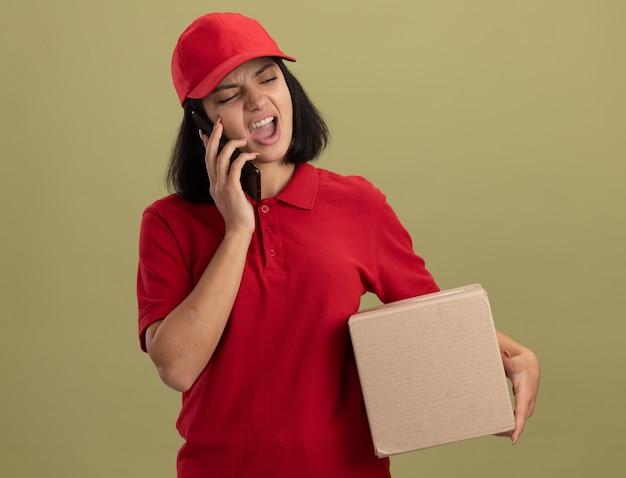 Giovane ragazza di consegna in uniforme rossa e cappuccio che tiene la scatola di cartone che grida mentre parla sul telefono cellulare che sta sopra la parete chiara