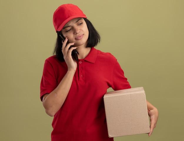 Giovane ragazza di consegna in uniforme rossa e cappuccio che tiene la scatola di cartone parlando al telefono cellulare essendo confusa e scontenta in piedi sopra la parete chiara