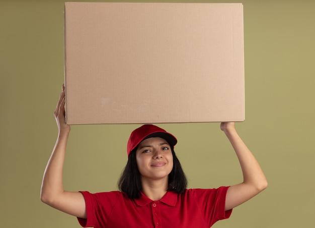 Giovane ragazza delle consegne in uniforme rossa e cappuccio che tiene grande scatola di cartone sopra la sua testa sorridente amichevole in piedi sopra la parete chiara