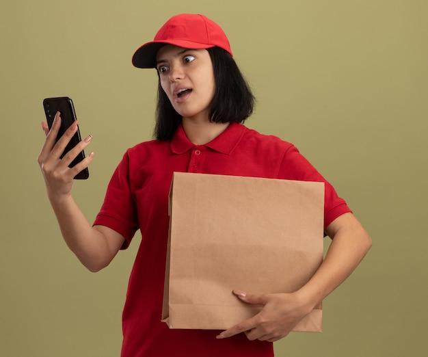 Giovane ragazza delle consegne in uniforme rossa e cappuccio che tiene il pacchetto di carta guardando il suo smartphone con espressione infastidita in piedi sopra la parete chiara