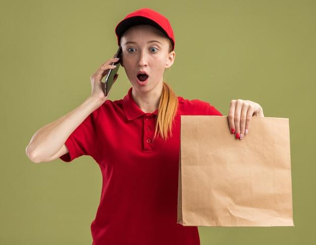 Giovane ragazza delle consegne in uniforme rossa e berretto con in mano un pacchetto di carta che sembra sorpresa mentre parla al cellulare su un muro verde green