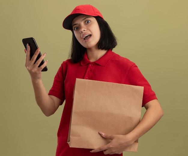Giovane ragazza di consegna in uniforme rossa e cappuccio che tiene il pacchetto di carta con lo smartphone sorpreso in piedi sopra la parete leggera