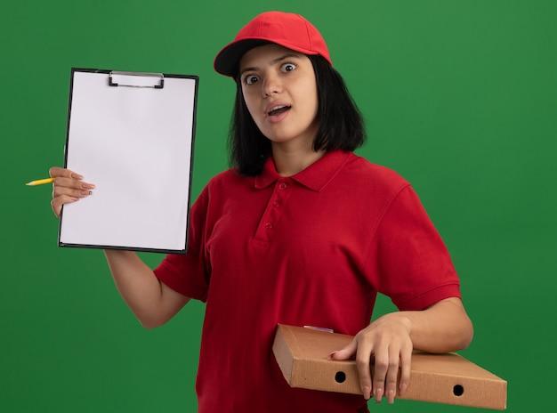 Giovane ragazza di consegna in uniforme rossa e cappuccio che tiene la scatola della pizza che mostra la lavagna per appunti con la matita sorpresa in piedi sopra la parete verde
