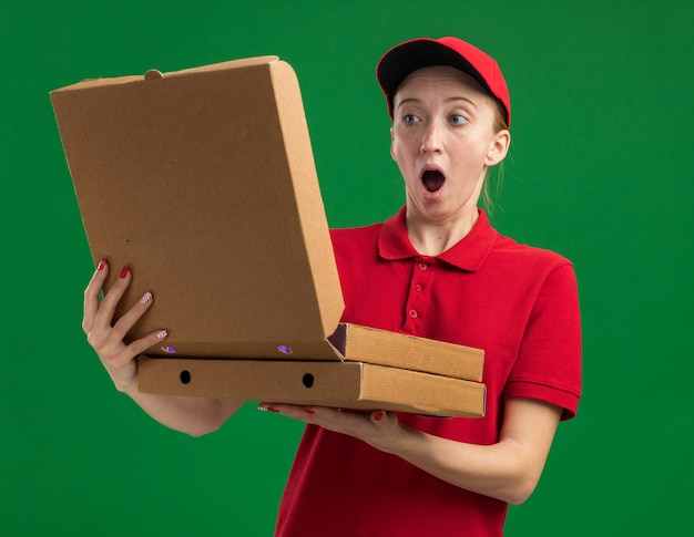 Giovane ragazza delle consegne in uniforme rossa e berretto che tiene in mano scatole per pizza che aprono una di quelle stupite e sorprese in piedi sul muro verde