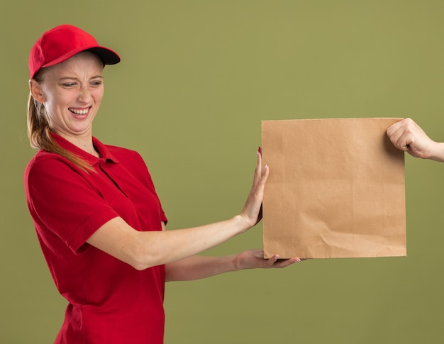 Young delivery girl in red uniform and cap refusing to receive paper package standing over green wall