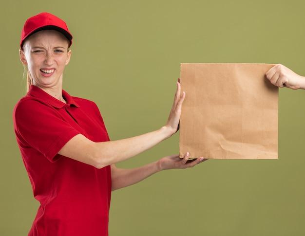 Giovane ragazza delle consegne in uniforme rossa e berretto che si rifiuta di ricevere un pacco di carta