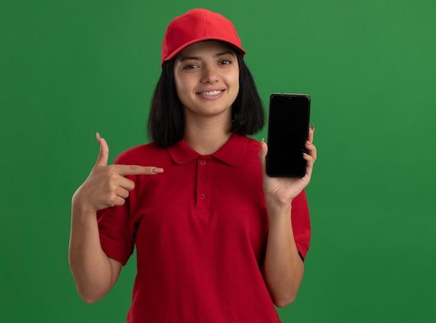Giovane ragazza di consegna in uniforme rossa e cappuccio che mostra smartphone che punta con il dito indice sorridendo fiducioso in piedi sopra la parete verde