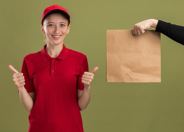 Giovane ragazza delle consegne in uniforme rossa e berretto sorridente che mostra i pollici in su mentre riceve un pacco di carta