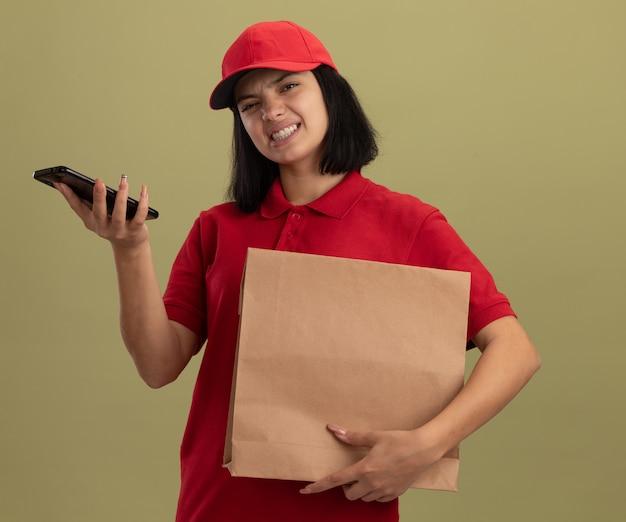 Giovane ragazza di consegna in uniforme rossa e cappuccio con smartphine che tiene il pacchetto di carta con espressione infastidita in piedi sopra la parete chiara