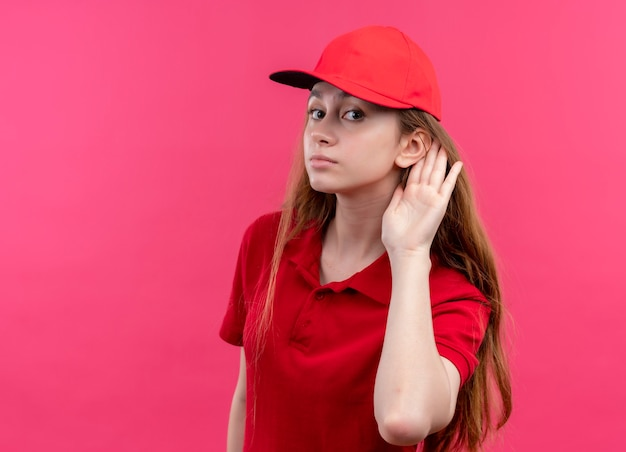 Young delivery girl in red uniform doing can't hear you on isolated pink wall with copy space