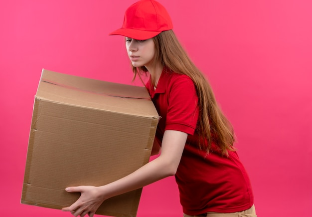 Giovane ragazza delle consegne in scatola di contenimento uniforme rossa guardando verso il basso e in piedi in vista di profilo sulla parete rosa isolata