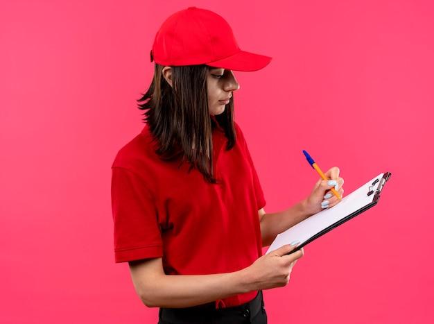 ピンクの壁の上に立って自信を持って何かを書くペンでクリップボードを保持している赤いポロシャツとキャップを身に着けている若い配達の女の子