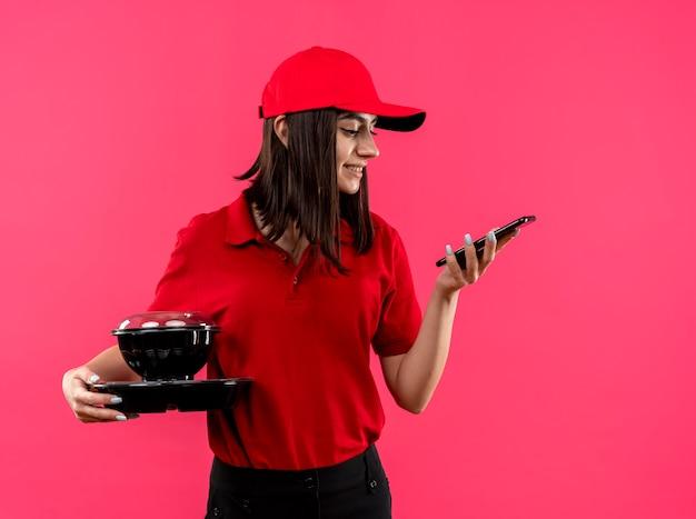 Молодая доставщица в красной рубашке поло и кепке держит пакет с едой, глядя на экран своего смартфона, улыбаясь, стоя над розовой стеной