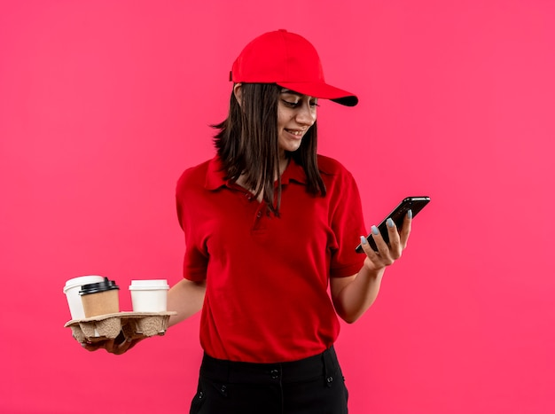 ピンクの壁の上に立って笑顔のスマートフォンの画面を見ている赤いポロシャツとフードパッケージを保持しているキャップを身に着けている若い配達の女の子