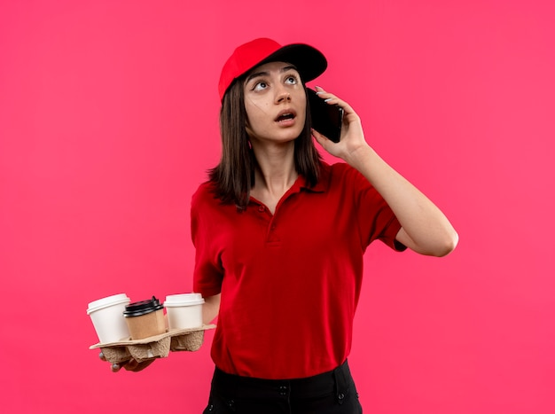 ピンクの壁の上に立っている携帯電話で話している間混乱しているように見える赤いポロシャツとフードパッケージを保持しているキャップを身に着けている若い配達の女の子