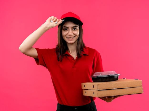 빨간 폴로 셔츠와 피자 상자와 분홍색 벽 위에 서있는 그녀의 모자를 만지고 행복한 얼굴로 웃는 음식 패키지를 들고 모자를 입고 젊은 배달 소녀