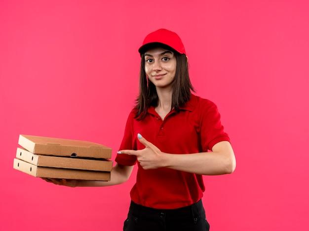 赤いポロシャツと帽子をかぶった若い配達の女の子は、ピンクの壁の上にフレンドリーに立って笑顔でそれらに人差し指で指しているピザボックスを保持しています
