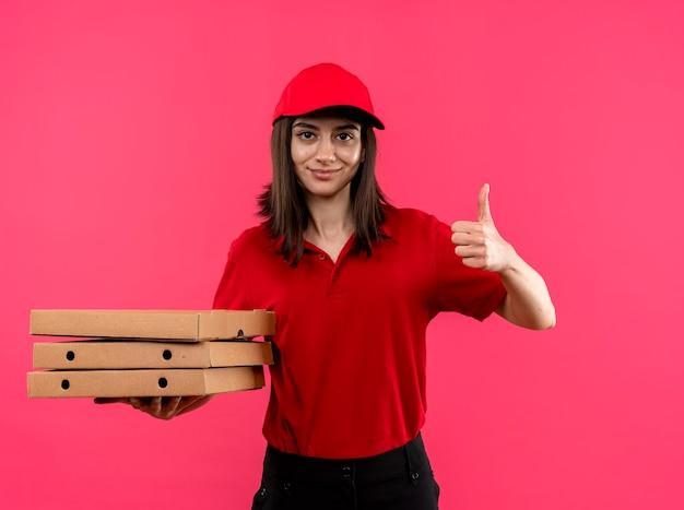 ピンクの壁の上に立って親指を見せて笑っているピザの箱を保持している赤いポロシャツと帽子を着て若い配達の女の子