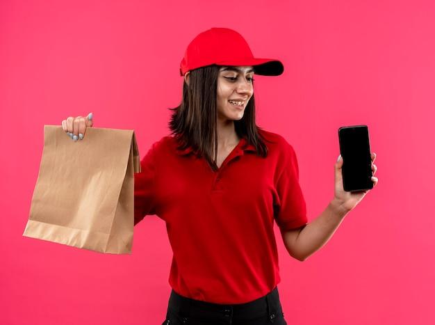분홍색 벽 위에 서있는 얼굴에 미소로 옆으로 찾고 빨간색 폴로 셔츠와 모자를 들고 스마트 폰과 종이 패키지를 입고 젊은 배달 소녀