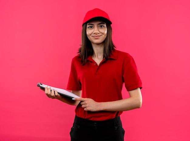 빨간 폴로 셔츠와 모자를 입고 젊은 배달 소녀 핑크 벽 위에 서있는 clipboar 서 웃고