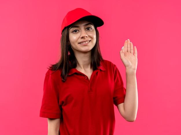 빨간 폴로 셔츠와 모자를 입고 젊은 배달 소녀 분홍색 벽 위에 서있는 손으로 흔들며 행복한 얼굴로 웃고