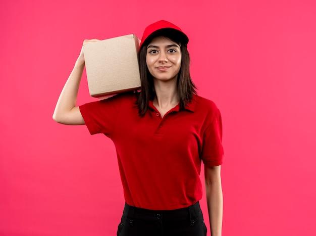 Giovane ragazza delle consegne che indossa la maglietta polo rossa e cappuccio che tiene il pacchetto della scatola sulla spalla con il sorriso sul viso in piedi sopra il muro rosa
