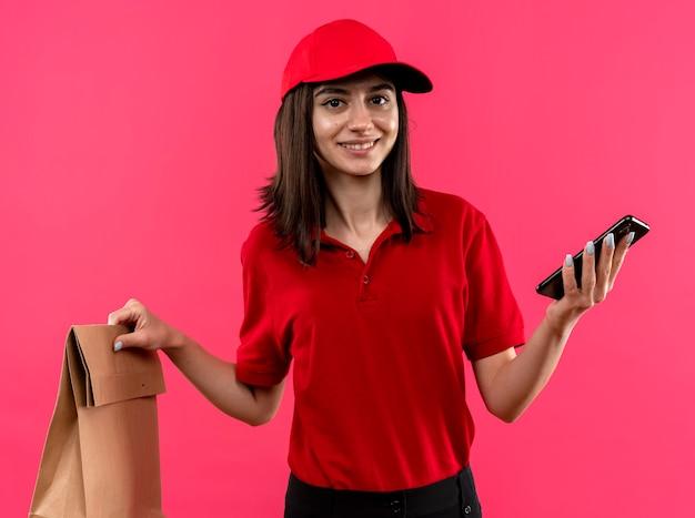 Giovane ragazza di consegna che indossa la maglietta di polo rossa e cappuccio che tiene il pacchetto di carta e lo smartphone sorridente in piedi amichevole sopra la parete rosa