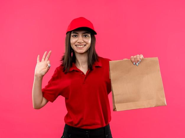 Giovane ragazza di consegna che indossa la maglietta di polo rossa e cappuccio che tiene il pacchetto di carta sorridente con la faccia felice che mostra segno giusto che sta sopra la parete rosa
