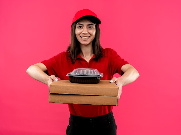 Young delivery girl wearing red polo shirt and cap holding pizza boxes and food package looking at camera smiling with happy face standing over pink background