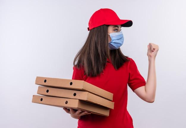 Молодая доставщица в красной футболке в красной кепке, носит маску для лица, держит коробку из-под пиццы и показывает кулак на белом фоне