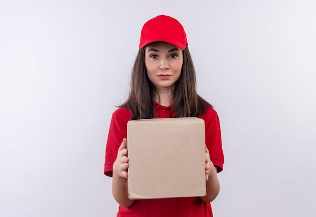 Молодая доставщица в красной футболке в красной кепке держит коробку на изолированном белом фоне